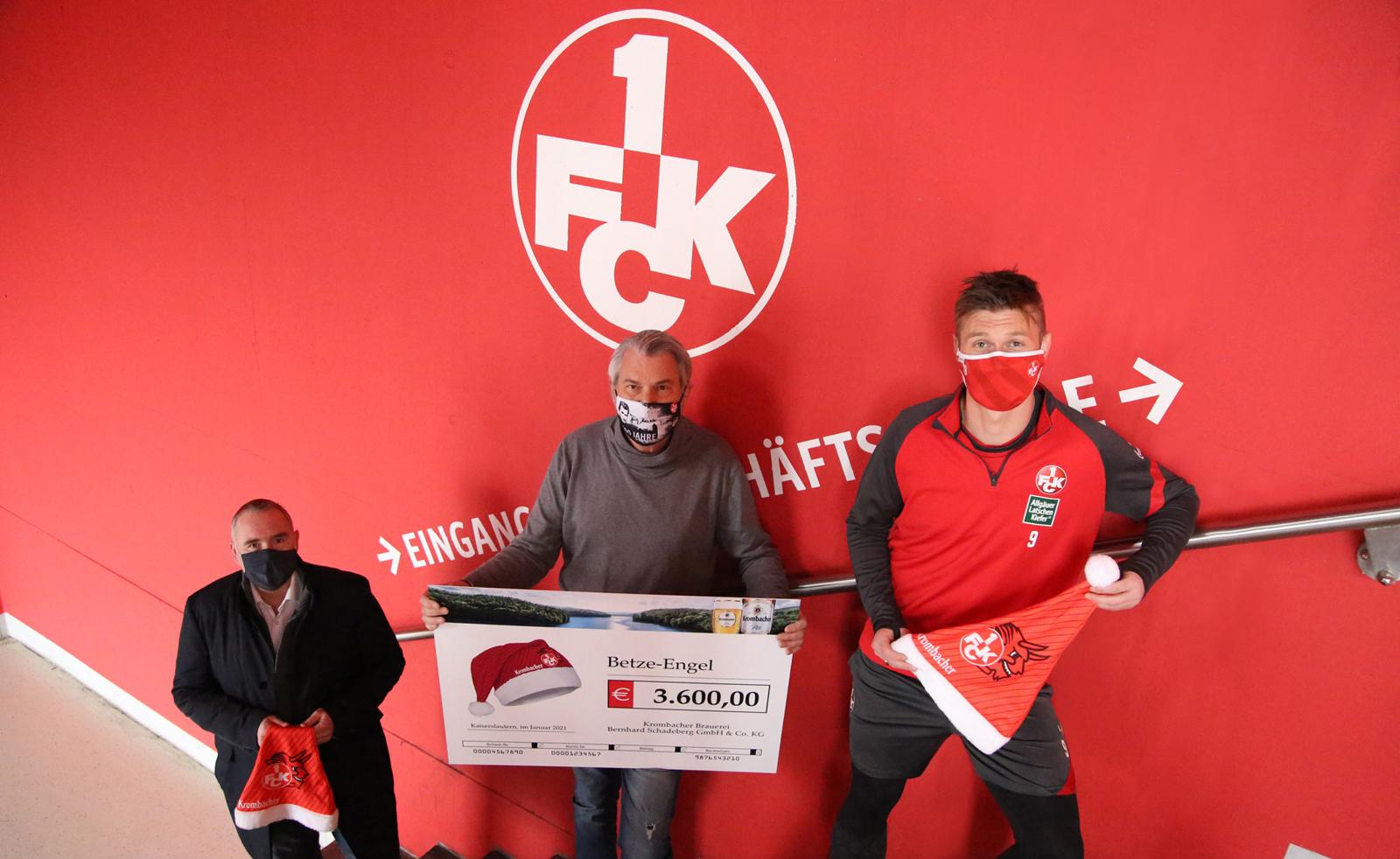 FCK-Stadionsprecher Horst Schömbs und Marvin Pourié nehmen den Spendenscheck von Krombacher für die Betze-Engel entgegen